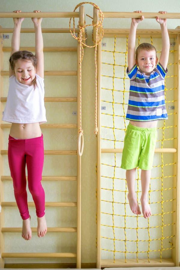 Enfants jouant et accrochant sur la barre horizontale photographie stock
