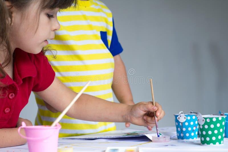 Enfants jouant et dessinant à la maison ou jardin d'enfants ou playschool photographie stock