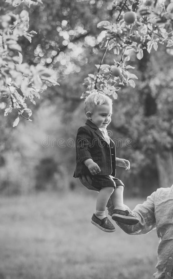 Enfants jouant - jeu heureux Le petit garçon s'asseyent sur la main masculine dans le jardin de pomme, confiance photographie stock