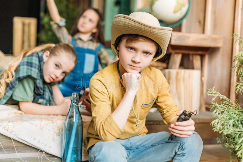 Enfants jouant la chasse à trésor avec la carte sur le porche photo stock