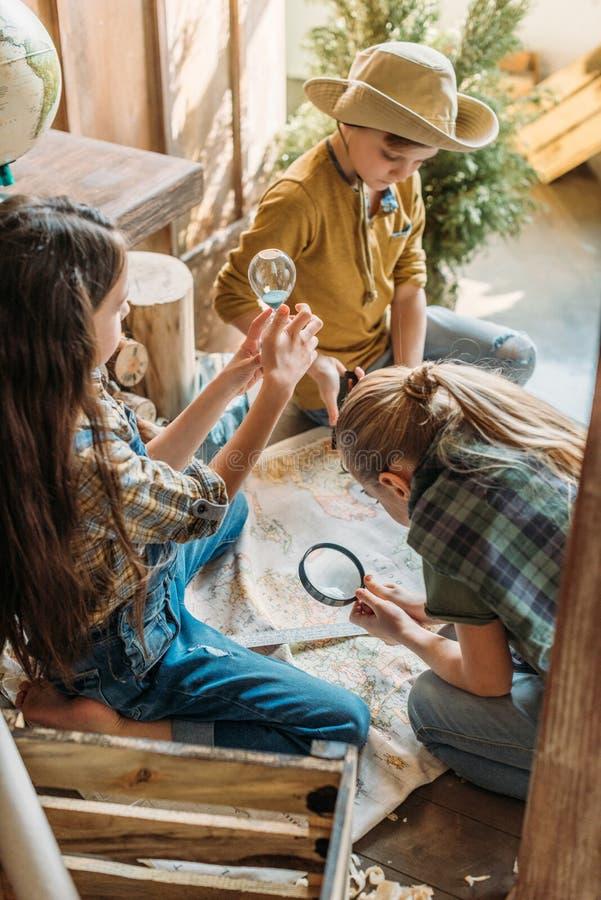 Enfants jouant la chasse à trésor avec la carte sur le porche image libre de droits