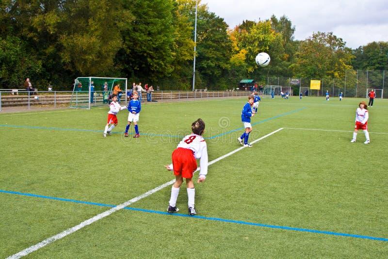 Enfants jouant le football image stock