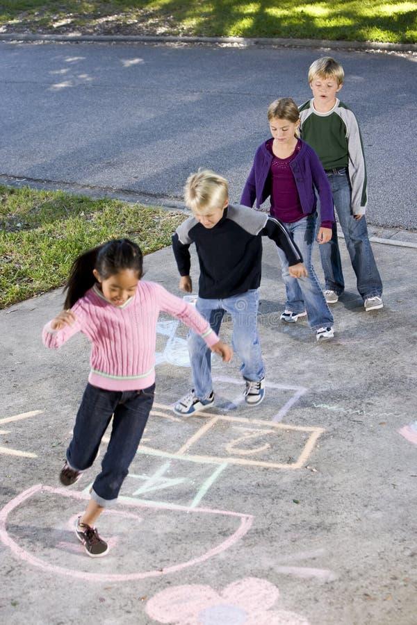 Enfants jouant le jeu de marelle photos stock