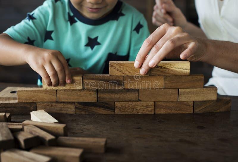 Enfants jouant le jouet en bois de bloc avec le professeur image libre de droits