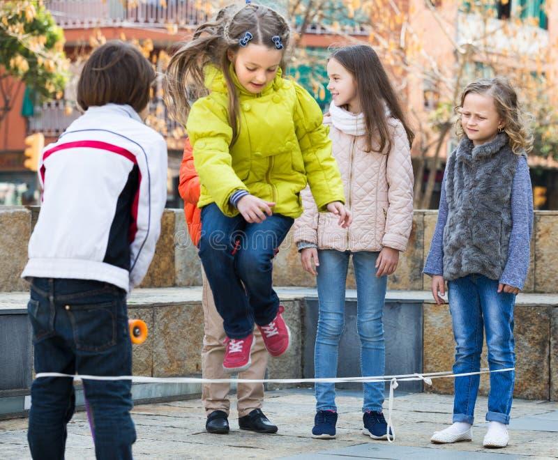 Enfants jouant sauter d'une bande élastique photos stock