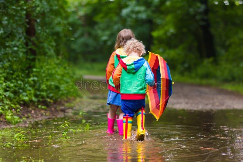 Enfants jouant sous la pluie avec le parapluie photo libre de droits
