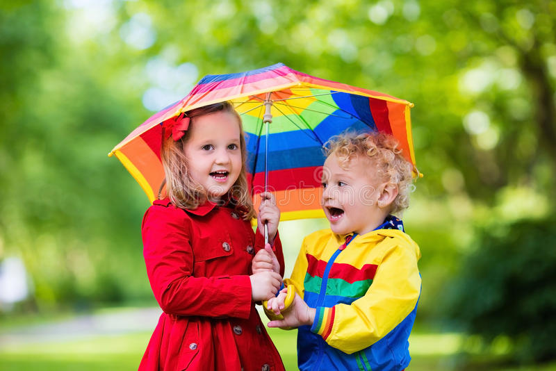 Enfants jouant sous la pluie sous le parapluie coloré images stock