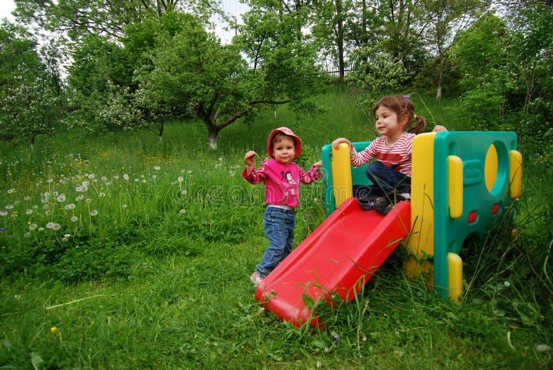 Enfants jouant sur la glissière photos stock