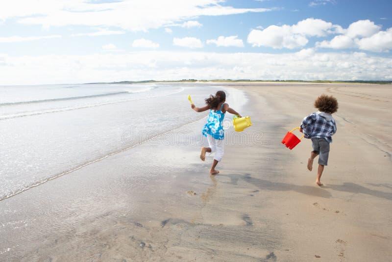 Enfants jouant sur la plage images stock