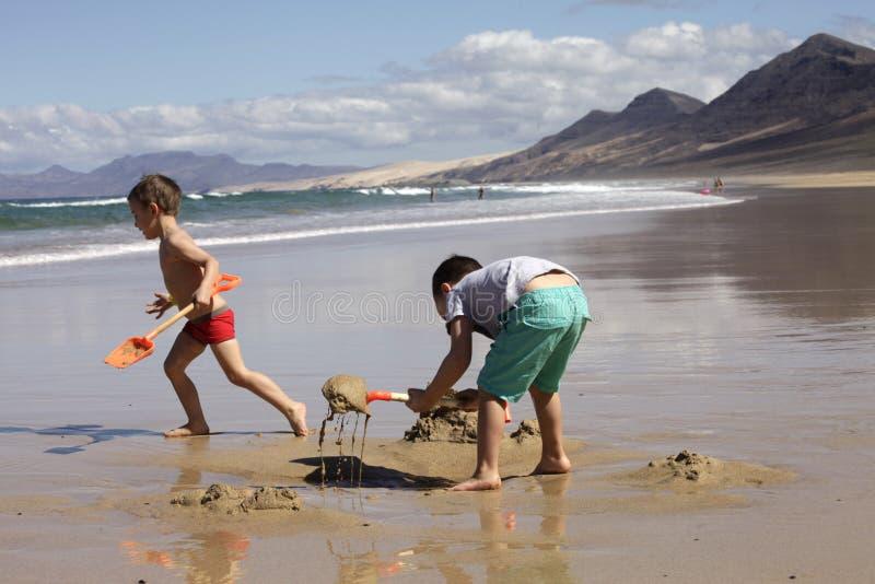 Enfants jouant sur la plage image libre de droits