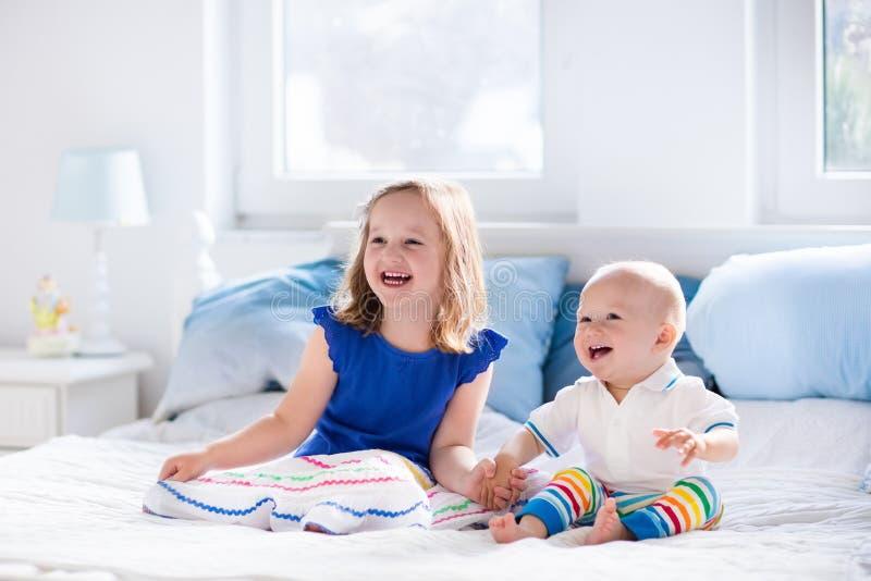 Enfants jouant sur le lit de parents photos libres de droits