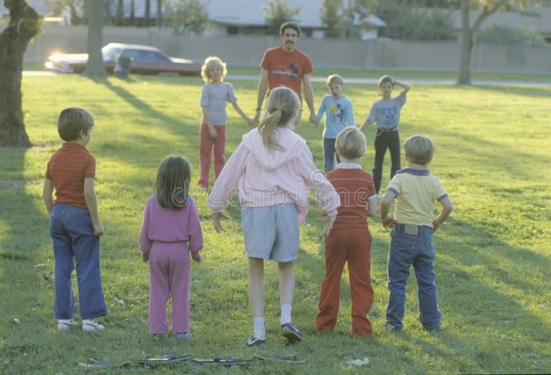 Enfants jouant un jeu à un parc public, verger de jardin, CA photographie stock libre de droits