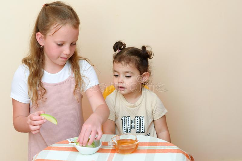 Enfants juifs plongeant des tranches de pomme dans le miel sur Rosh HaShanah photos stock