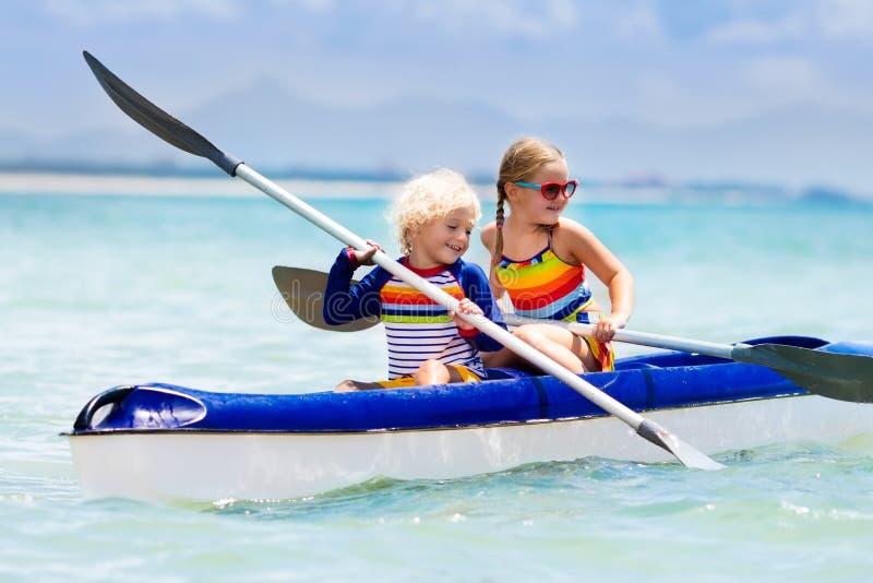 Enfants kayaking dans l'océan Enfants dans le kayak en mer tropicale image libre de droits