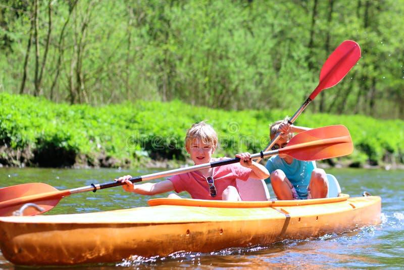 Enfants kayaking sur la rivière image stock