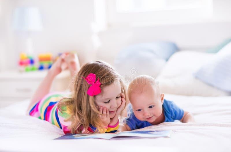 Enfants lisant dans la chambre à coucher blanche photos libres de droits