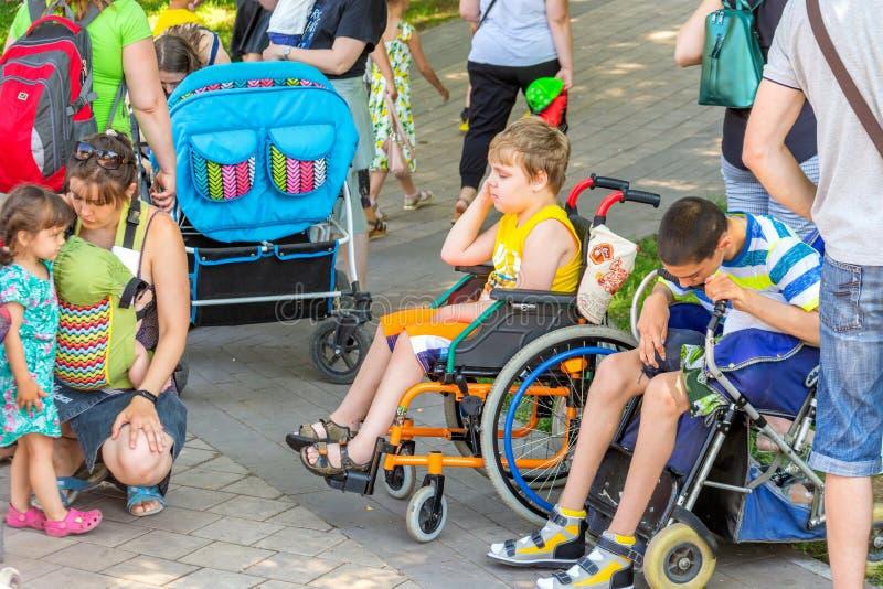 enfants malades dans une promenade de fauteuil roulant en parc à un festival de ville images libres de droits
