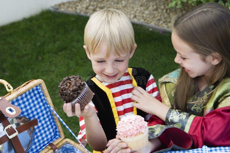 Enfants mangeant des petits gâteaux images stock