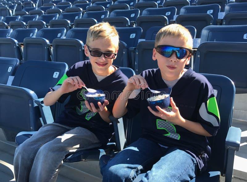 Enfants mangeant la crème glacée au parc vide de base-ball images libres de droits
