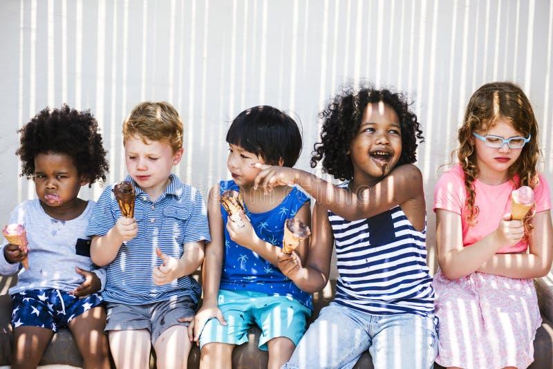 Enfants mangeant la crème glacée pendant l'été image libre de droits