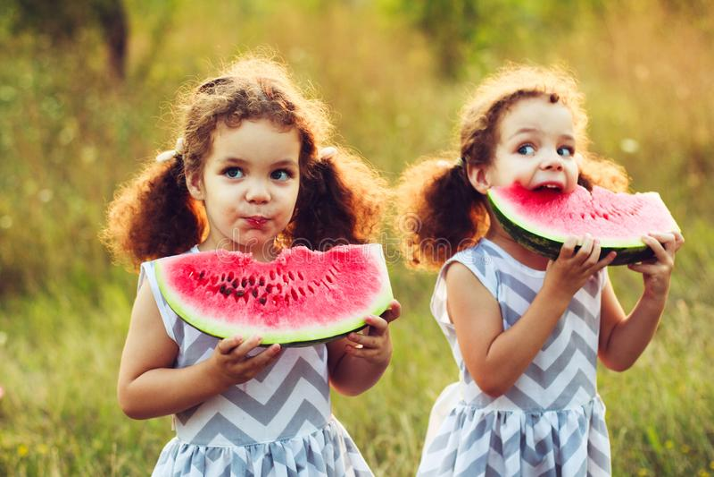 Enfants mangeant la pastèque en parc Les enfants mangent du fruit dehors Casse-croûte sain pour des enfants Petits jumeaux jouant images stock