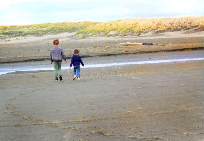 Enfants marchant à la plage images stock