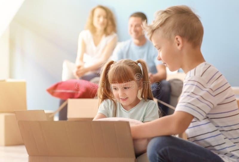 Enfants mignons déballant la boîte après entrée dans la nouvelle maison photographie stock libre de droits
