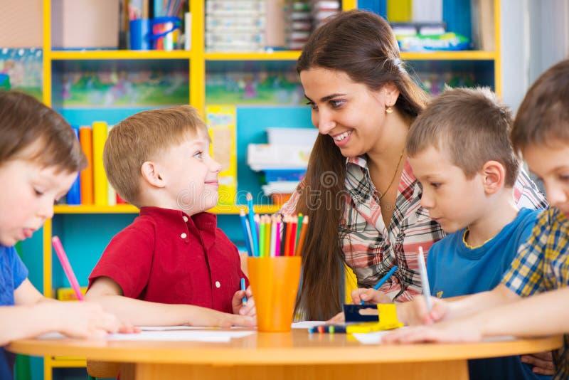 Enfants mignons dessinant avec le professeur à la classe préscolaire image libre de droits
