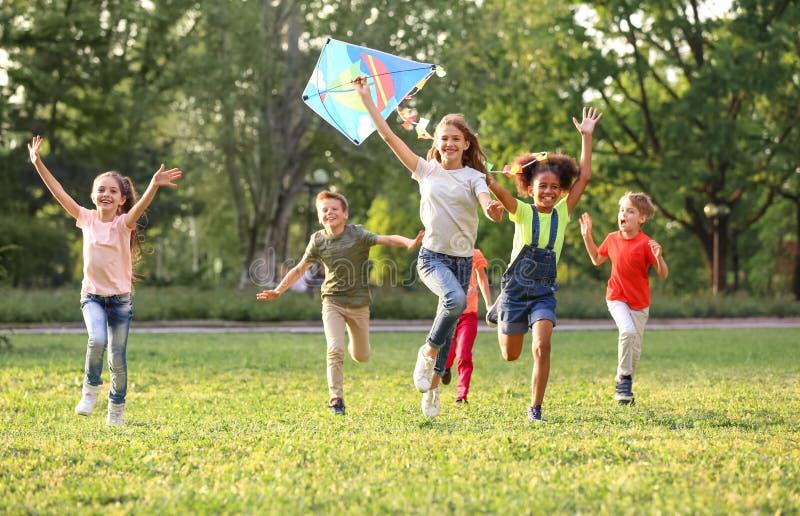 Enfants mignons jouant avec le cerf-volant dehors le jour ensoleillé images stock