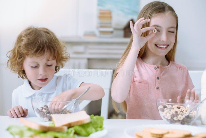 Enfants mignons mangeant leur petit déjeuner sain photo stock