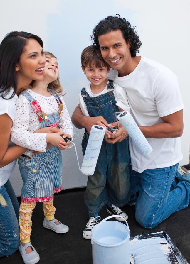 Enfants mignons peignant une salle avec leurs parents photographie stock