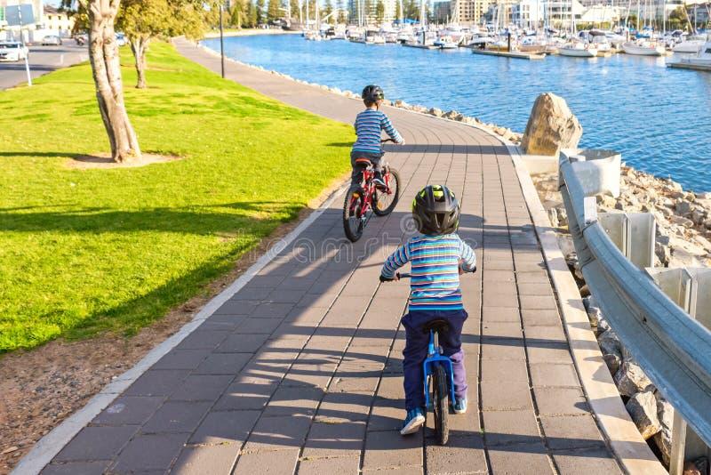 Enfants montant des bicyclettes dans Glenelg image libre de droits