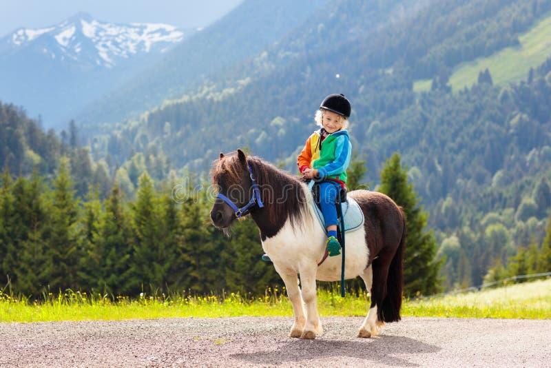 Enfants montant le poney Enfant sur le cheval en montagnes d'Alpes photos stock