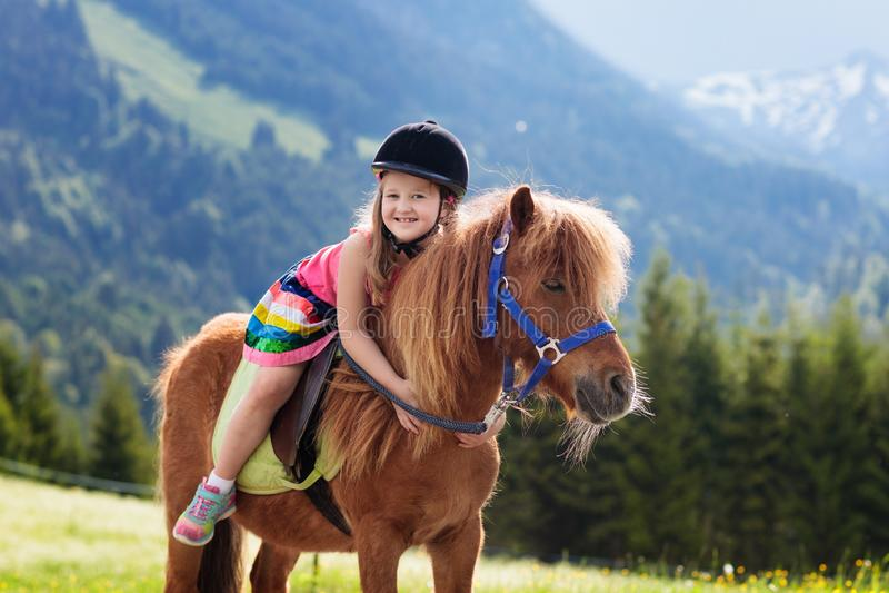 Enfants montant le poney Enfant sur le cheval en montagnes d'Alpes photographie stock