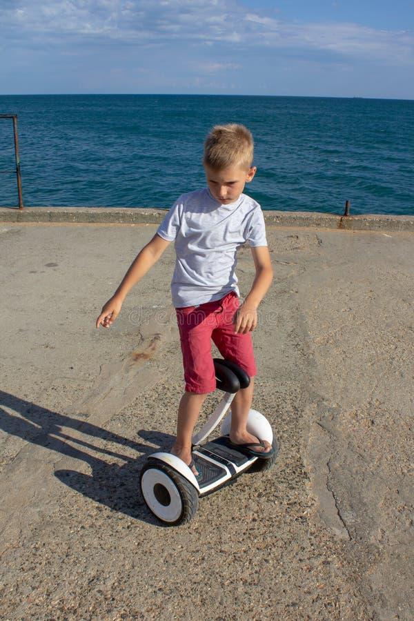 Enfants montant le scooter en été près de la mer Panneau d'équilibre pour des enfants Nouvelles technologies modernes de transpor images libres de droits