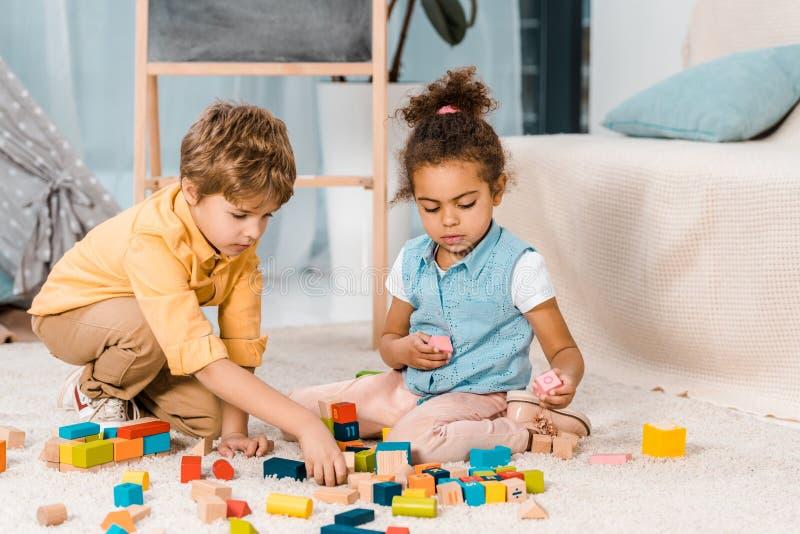 enfants multi-ethniques adorables jouant avec les blocs en bois colorés photographie stock libre de droits