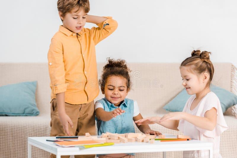 enfants multi-ethniques adorables jouant avec les blocs en bois photos stock