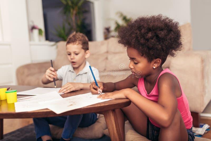 Enfants multiraciaux dessinant à la maison photo stock