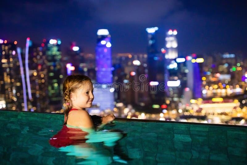 Enfants nageant dans la piscine extérieure supérieure de toit des vacances de famille à Singapour Horizon de ville de piscine d'i image libre de droits