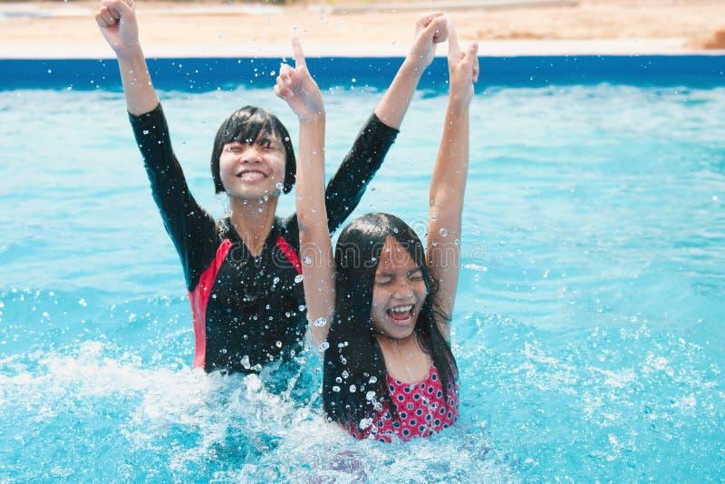 enfants nageant et jouant dans la piscine avec heureux image libre de droits