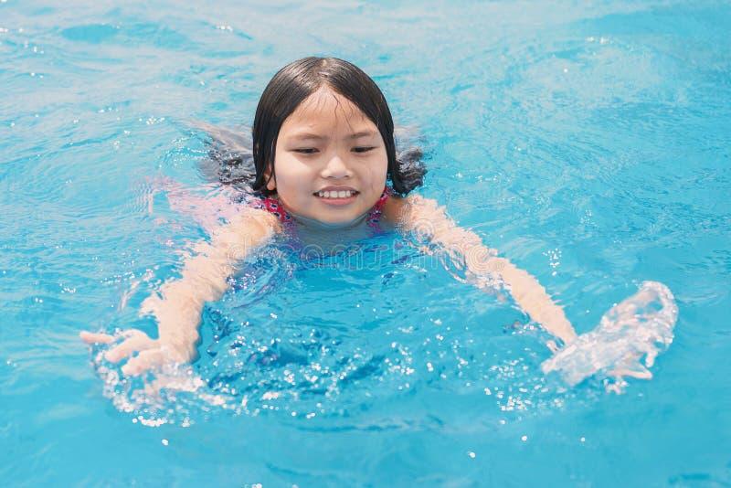 enfants nageant et jouant dans la piscine avec heureux images stock