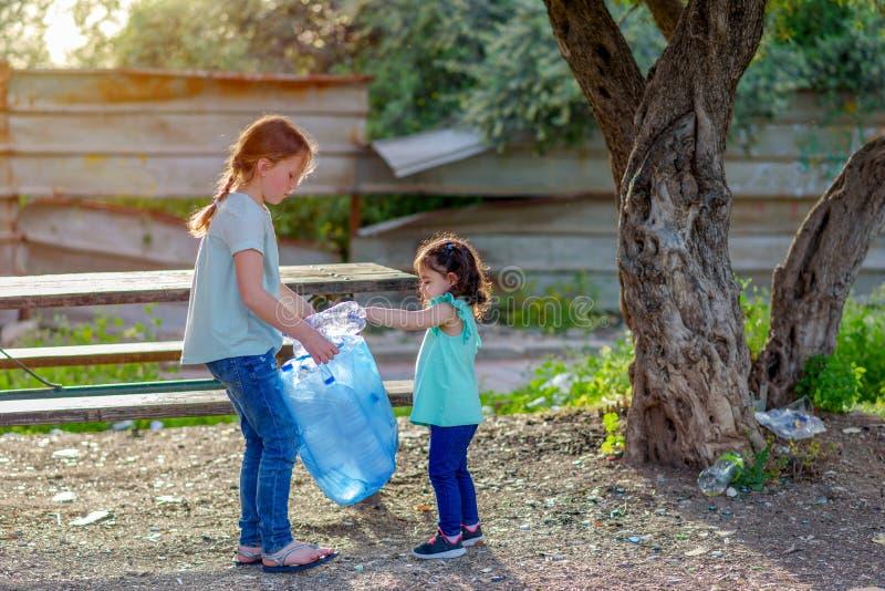 Enfants nettoyant en parc Enfants volontaires avec un sac de d?chets nettoyant des ordures, mettant la bouteille en plastique en  photo stock