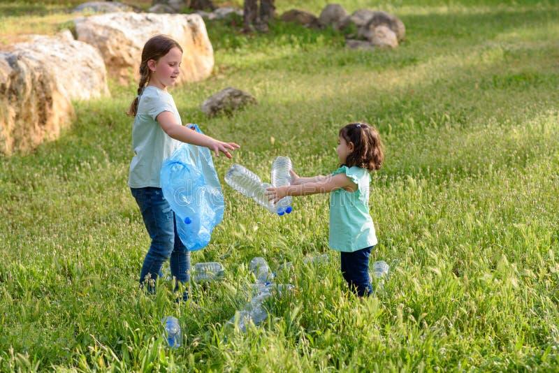 Enfants nettoyant en parc Enfants volontaires avec un sac de d?chets nettoyant des ordures, mettant la bouteille en plastique en  images stock