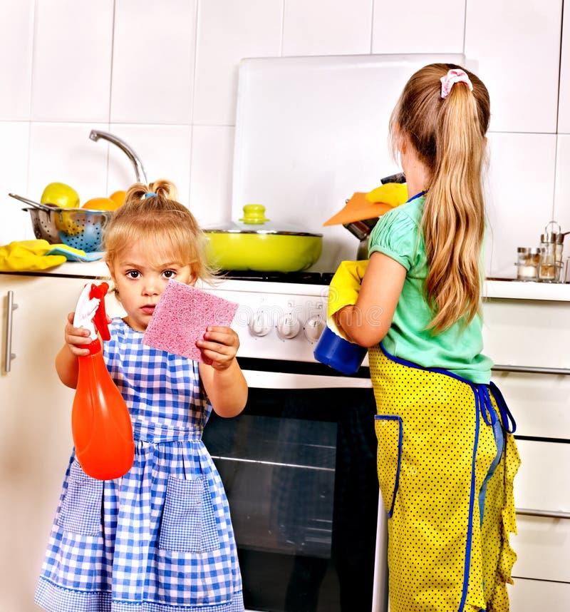 Enfants nettoyant la cuisine. image stock