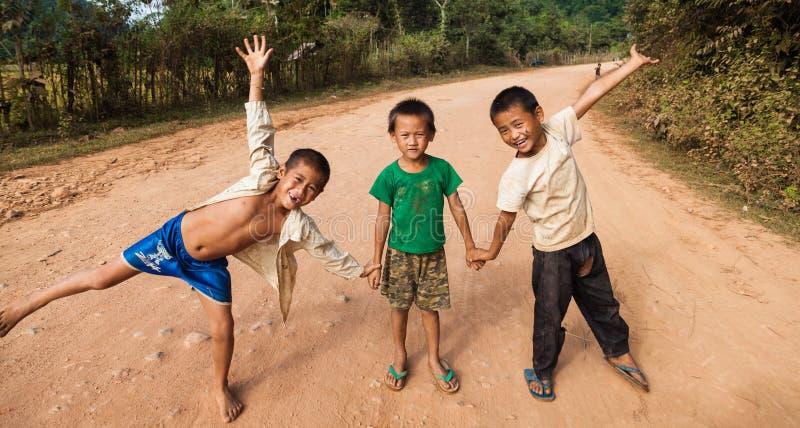 Enfants non identifiés posant sur une route dans Vang Vieng image libre de droits