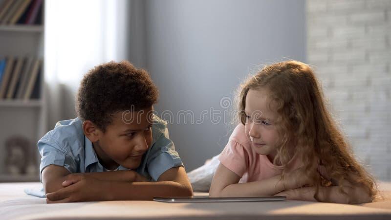 Enfants observant l'exposition sur le comprimé en hésitant, regardant l'un l'autre embarrassant image stock