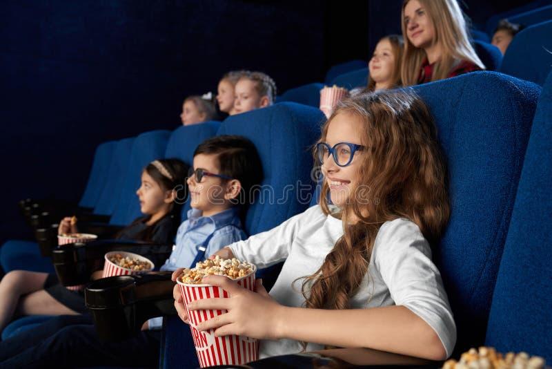 Enfants observant le film dans le cinéma, tenant des seaux de maïs éclaté image stock