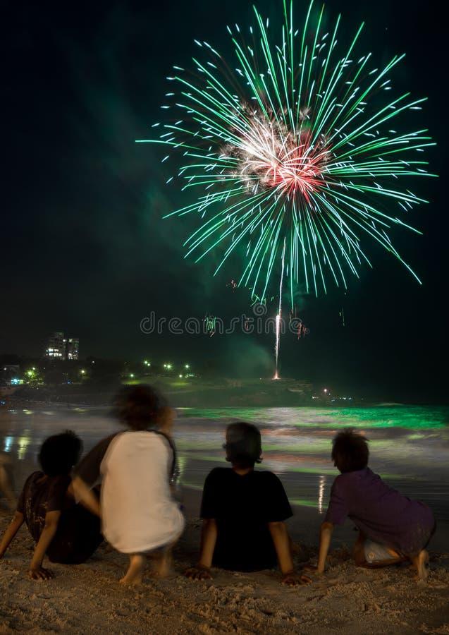 Enfants observant les feux d'artifice par la plage la soirée du Nouveau an photo stock