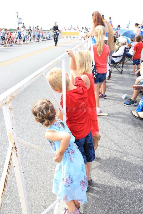 Enfants observant un d?fil? de Jour de la D?claration d'Ind?pendance photographie stock libre de droits