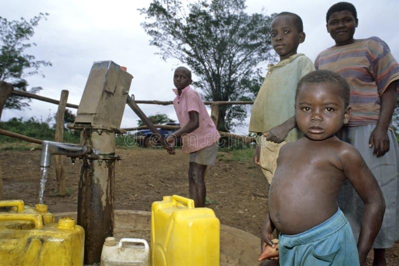 Enfants ougandais cherchant l'eau à la pompe à eau photos stock
